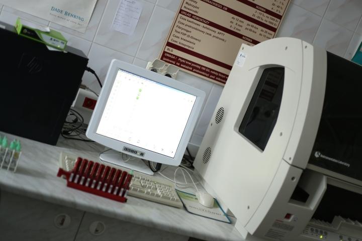 na biurku koloru białego znajdują sie fiolki z badaniami koloru czerwonego oraz szary aparat do badań laboratoryjnych z monitorem koloru białego