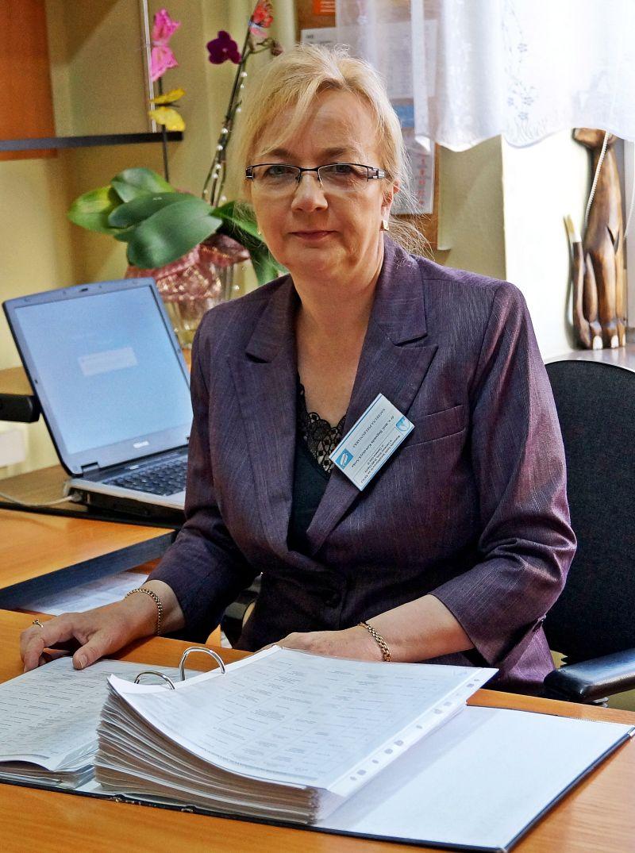 naczelna pielęgniarka w biurze przy biurku koloru brązowego z dokumentacją oraz laptopem