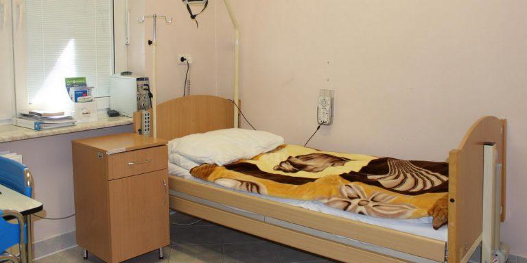 pokój pracowni snu w którym znajduję się łóżko medyczne koloru brązowego wraz dwoma krzesłami koloru niebieskiego i białymi drzwiami wyjsciowymi