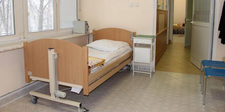 pokój pracowni snu w którym znajduję sięłóżko medyczne koloru brązowego wraz dwoma krzesłami koloru niebieskiego i białymi drzwiami wyjsciowymi