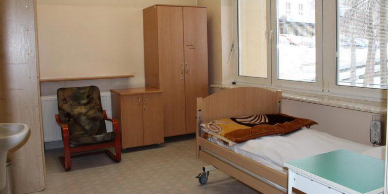 pokój pracowni snu koloru biaego w którym znajdujęą sie meble koloru brązowego oraz łóżko medyczne koloru brązowego
