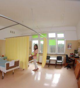 sala oddziału szpitala koloru żółtego z zielonymi roletami w oknach na której znajdują się żółte parawany biurko koloru brązowego wraz czarnym fotelem obrotowym stoi osoba ubrana w różową odzież ochronna