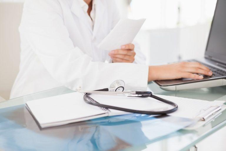 sylwetka czlowieka ubrana w białe ubranie ochronne medyczne przy biurko na którym znajduje się laptop koloru czarnego dokumentacja medyczna oraz stetyskop koloru czarnego