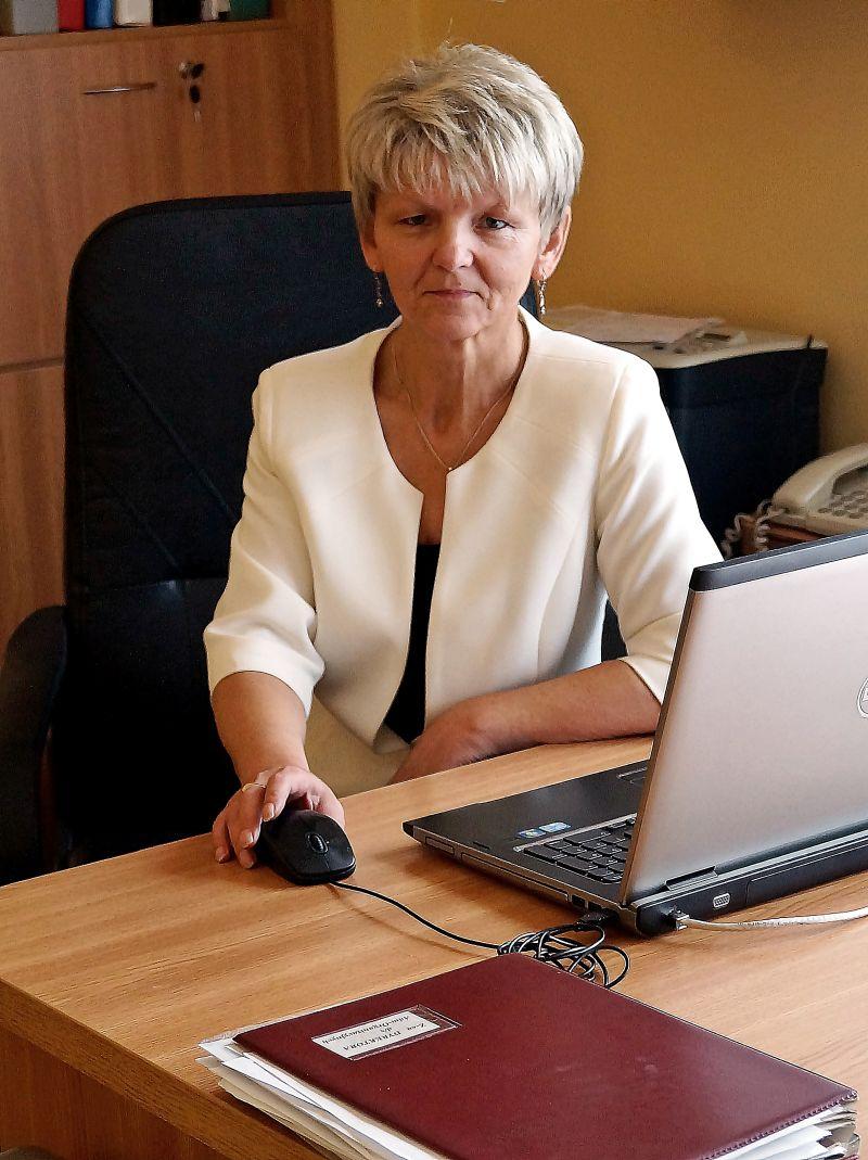 Zastępca Dyrektora ds. Administracyjno - Orgranizacyjnych ubrana w ubranie wizytowe w biurze przy biurku koloru brązowego z laptopem koloru srebnego