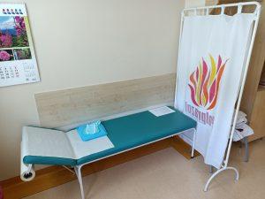 pomieszczenie poradni alergicznej wyposażone w leżak madr=yczny koloru niebieskiego obok biały parawan