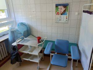 w pomieszczeniu znajduje się fotel obrotowy niebieski wraz z zieloną leżanka medyczną i białem parawanem i wózkiem medycznym na którym znajduje się czerowny pojemik medyczny.