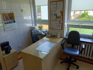 pokój koloru białego w którym znajduję się biurko kolou brazowego wraz z dwoma fotelami obrotowymi koloru czarnego.