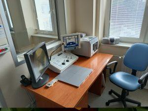 fotel obrotowy koloru niebieskiego wraz z brazowym biurkiem na którym znajduję się kokpit sterowniczy wraz z monitorem do badań RTG.