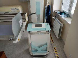aparat rtg koloru szaro turkusowego wraz z łózkiem medycznym koloru szarego