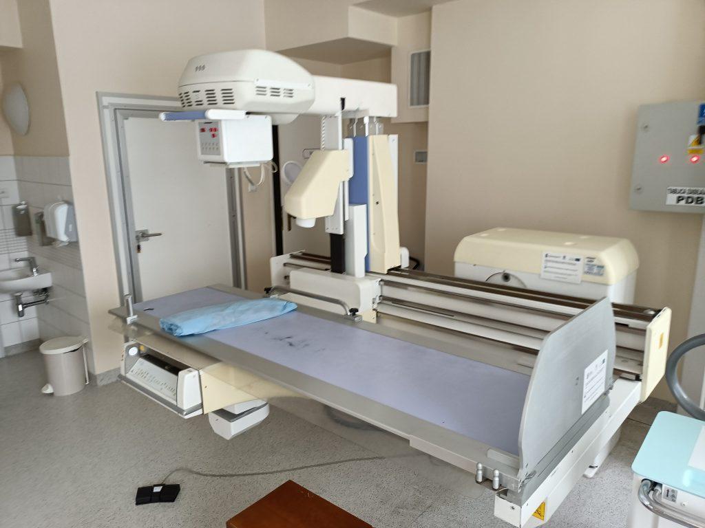 aparat do badań RTG w pracowni RTG oraz drzwiami wyjściowymi koloru białego
