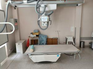 pracownia rtg wraz z aparatem do badaniań i białem łóżkiem do diagnostyki RTG