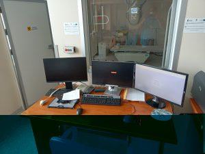 pokój techników RTG z brązowym biurkiem i sprzetem komputerowym oraz szybą podglądową do aparatu badań RTG