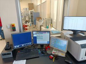 pokój techników RTG zbrązowym biurkiem i sprzetem komputerowym