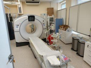 Pracownia TK wyposażona w Tomograf Komputerowy koloru białego obok wózek medyczy koloru białego wraz z prawanem koloru niebiekiego oraz drzwiami koloru białego