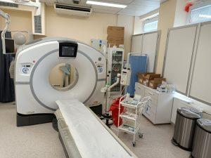 Pracownia TK wyposażona w Tomograf Komputerowy koloru białego obok wózek medyczy koloru białego wraz z prawanem koloru niebiekiego