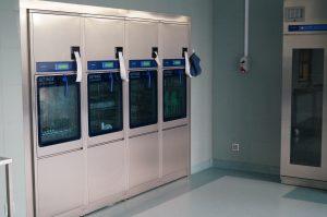 urządzenie koloru szarego do sterylizacji narzędzie medycznych w pomieszczeniu koloru niebieskiego
