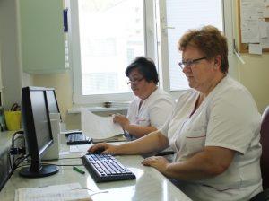 dwie pielęgniarki ubrane w białe ubrania ochronne podczas pracy w systemie szpitalnym przy monitorach i klawiaturach koloru czarnego.
