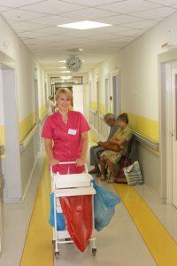 korytarz oddziału szpitalnego z pielęgniarką w różowym ubraniu z wózkiem medycznym koloru białego oraz dwie osoby w tle