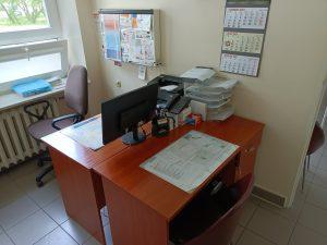 pomieszczenie poradni chirurgicznej wyposażoen w dwa biurka koloru brązowego na którym znajduję się sprzęt komputerowy obok fotel obrotowy koloru brązowego