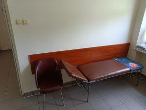 pomieszczenie poradni chirurgicznej wraz z leżakiem medycznym i krzesłem koloru brążowego