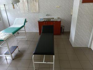 pomieszczenie poradni chirurgicznej w którym znjaduję sie dwie leżanki medyczne koloru czarengo i zielonego wraz z umywalką do mysia rąk koloru brązowego