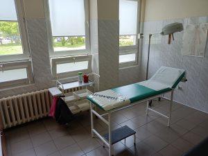 pomieszczenie koloru białego w którym znajduję się leżak medyczny koloru niebieksiego wraz z wózkiem medycznym koloru białego