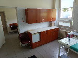 pomieszczenie poradni chirurgicznej wyposażone meblosciankę koloru brązowego oraz dwa krzesełka koloru brązowego oraz leżakmedyczny koloru niebieskiego.