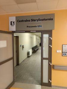 drzwi koloru szarego z przejściem do Pracowni USG na korytarzu koloru szarego