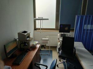 Pomieszczenie pracowni USG wyposażone w fotel obrotowy koloru czarnego wraz z leżakiem medycznym kolory niebieskiegi oraz aprataem do badań USG oraz biurkiem ze sprzetem komputerowym i drukarką.