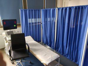 Aparat do badań USG obok którego znajduję się łózko medyczne koloru białem z parawanami koloru niebieskiego i fotelem obrotowym koloru czarnego.