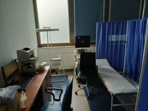 Pomieszczenie pracowni USG w którym znajduję się łóżko medyczne koloru białegoz niebieskim parawanem wraz z aparatem do badań usg, fotelem obrotowym kolory czarnego i biurkiem na którym znajduje sie sprzęt komputerowy z drukarką.