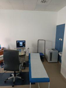 Pomieszczenie pracowni USG wyposażone w fotel obrotowy koloru czarnego wraz z leżakiem medycznym kolory niebieskiegi oraz aprataem do badań USG.