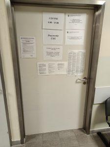 dzwi koloru szarego wraz z adnotacjami przyjęć pacjentów do pracowni USG.