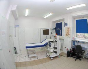 leżak medyczny koloru biało niebieskiego obok monitor koloru białego z wózkiem na którym znajduję sie aparat do gastroskopii oraz biurko z zestawem komputerowym