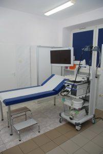 leżak medyczny koloru biało niebieskiego obok monitor koloru białego z wózkiem na którym znajduję sie aparat do gastroskopii