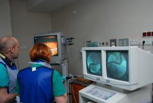 dwie osoby w ubranich koloru niebieskiego ogląda wykonywaną operację na monitorach aparatu endoskopowego