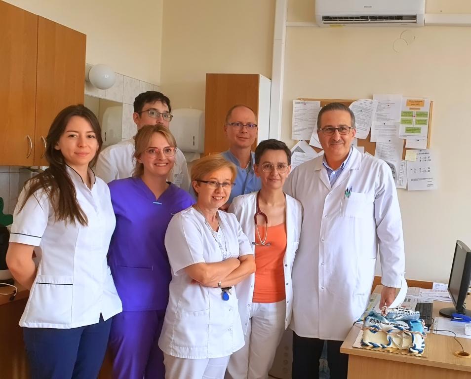 Personel lekarski. Cztery kobiety oraz trzech mężczyzn, wszyscy uśmiechnięci pozują do zdjęcia. Jedna posiada stetoskop na szyi. Przebywają w pokoju lekarskim.