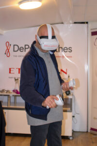 Mężczyzna z goglami do wirtualnej rzeczywistości na oczach, oraz kontrolerami w rękach