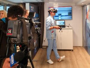 Lekarz w niebieskim ubraniu ochronnym. Na głowie ma okulary do Wirtualnej Rzeczywistosci.